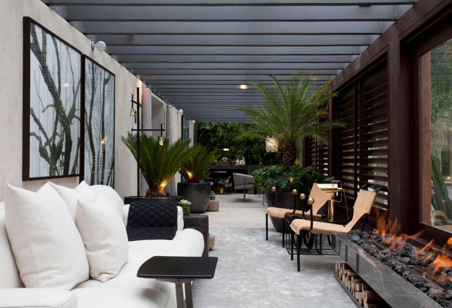 Terraço Gourmet - Joana Requião. O ambiente prolonga o living, e seu sentido horizontal foi explorado pela lareira embutida. Nas paredes, o revestimento é de limestone.