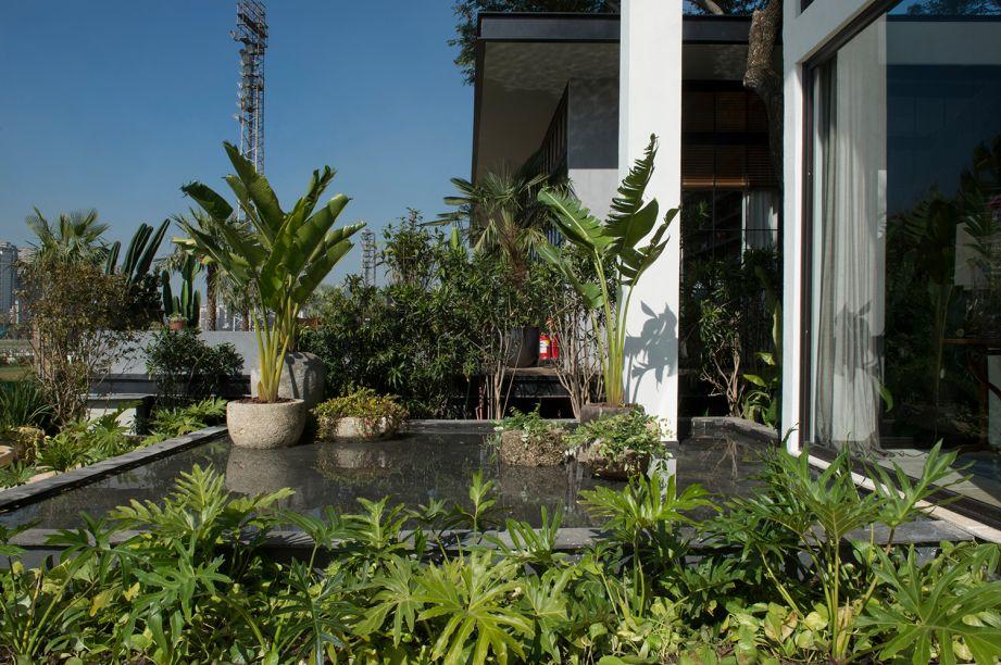 Jardim da Casa - Bia Abreu. Filodendros, samambaias e bananeiras compõem um jardim tropical e não tão certinho, que reúne vasos de pedra em uma varanda externa com banco. Um jardim vertical que reflete no espelho d´água durante a noite, completa a proposta.