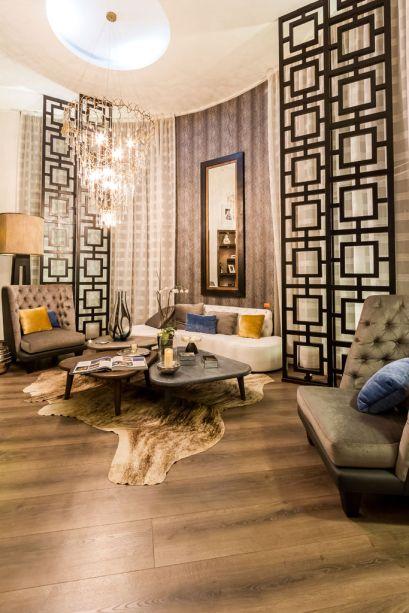 Casa Cor Bolívia 2015: Lobby por Maya Mc Lean - Maya se inspirou em um hotel boutique para criar um ambiente de estilo moderno, quente, com materiais naturais, como madeiras entalhadas, texturas, couros e acabamentos nas cores cinza e café. A iluminação escolhida é quente, com lustres e candeiros. Nas paredes, revestimentos de madeira e papel de parede texturizado de pele de anaconda, que combina com o tapete de couro.