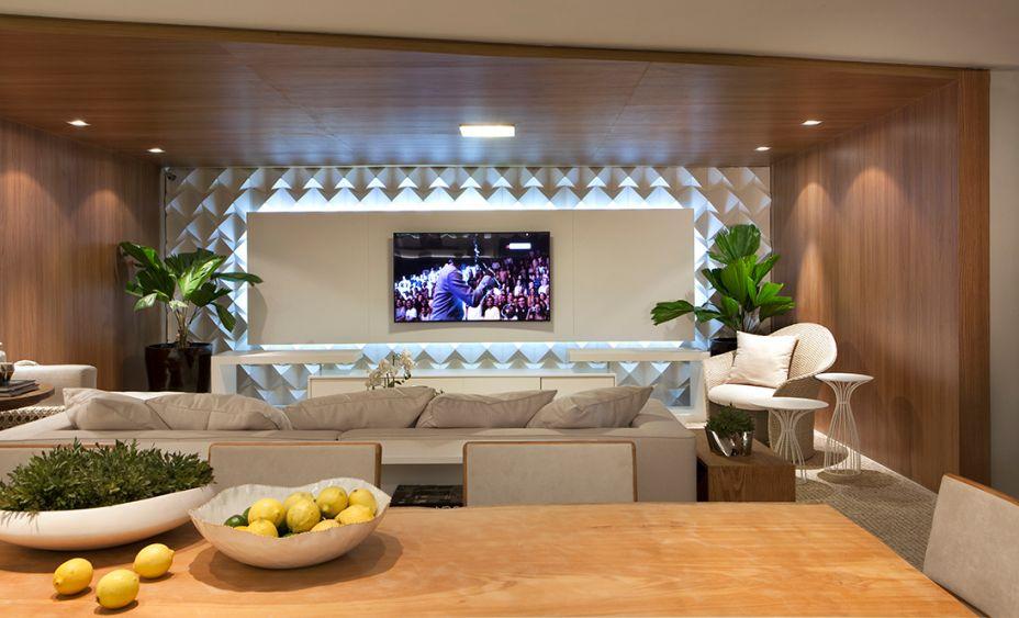 Refúgio do Jovem Casal - Isabele Melo. Com 70 m², o ambiente permite cozinhar e receber amigos com descontração e conforto. Revestimentos 3D, como o utilizado no painel da TV, ganham destaque graças à iluminação. E a marcenaria ultrapassa os limites tradicionais ao revestir também a parede e o teto.