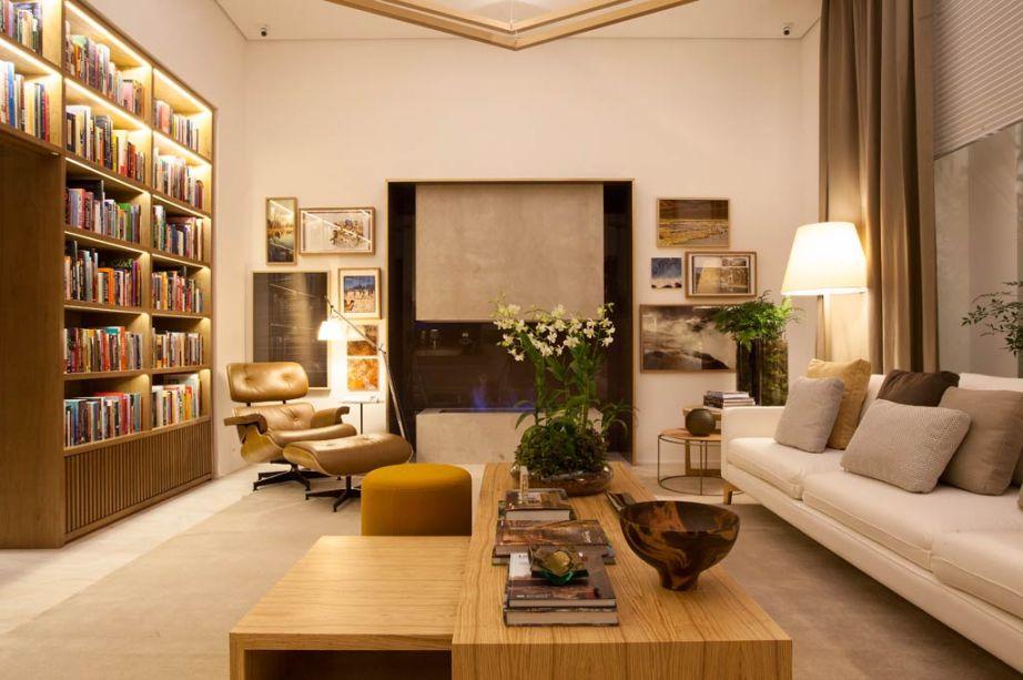 """Bruno Gap, Biblioteca de Estar. O arquiteto recebeu a tarefa de rechear os 35 m2 do espaço na CASA COR SÃO PAULO com livros criando uma grande biblioteca. Para chegar ao ambiente, os visitantes terão que passar por um corredor estreito com teto baixo, revestido de espelhos. """"Ao adentrar a biblioteca, as pessoas vão se surpreender com a altura de 3,5m do pé-direito"""", conta Gap. Tons terrosos, dos mais claros aos mais escuros, formam a paleta de cores dos revestimentos e móveis. A iluminação baixa e a lareira à álcool da Largrill contribuem para um clima aconchegante e intimista. """"É um living com biblioteca em anexo, ou vice-versa, onde os moradores podem relaxar, ler um livro e escutar uma música"""", explica. La Lampe, Breton Actual, Estar Móveis e Amorim Cortinas são alguns dos parceiros de Bruno Gap na concepção do espaço."""