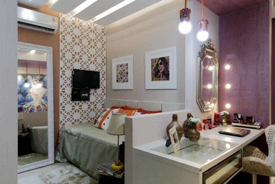 CASACOR Alagoas 2015. Suíte da Neta Blogueira - Ana Clara Costa, Carol Alves e Marilia Duarte. A bancada pode ser utilizada como mesa de trabalho e penteadeira, localizada na junção entre o espaço de dormir e o closet. A poltrona foi customizada artesanalmente e também direciona o olhar para o papel de parede na cor berinjela, que demarca esse cenário. Acima da cama, chama a atenção o desenho do gesso no teto, bem como o revestimento da parede de TV, que faz uma releitura da renda filé. A cama conta com uma cabeceira acolchoada em linho e é articulada, oferecendo todo o conforto.