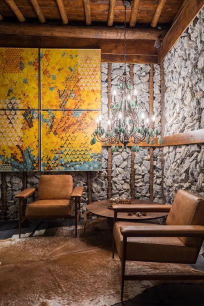 Living: Melina Mundim. Um pergolado de eucalipto define o ambiente, que possui paredes de gabião, além de piso e forro em madeira, elementos típicos do Brasil. Poltronas em couro, tapete de pele, almofadas bordadas e outros itens afirmam o aconchego e criam pequenos ambientes de convivência dentro do estar. O pendente é de cristal de rocha.