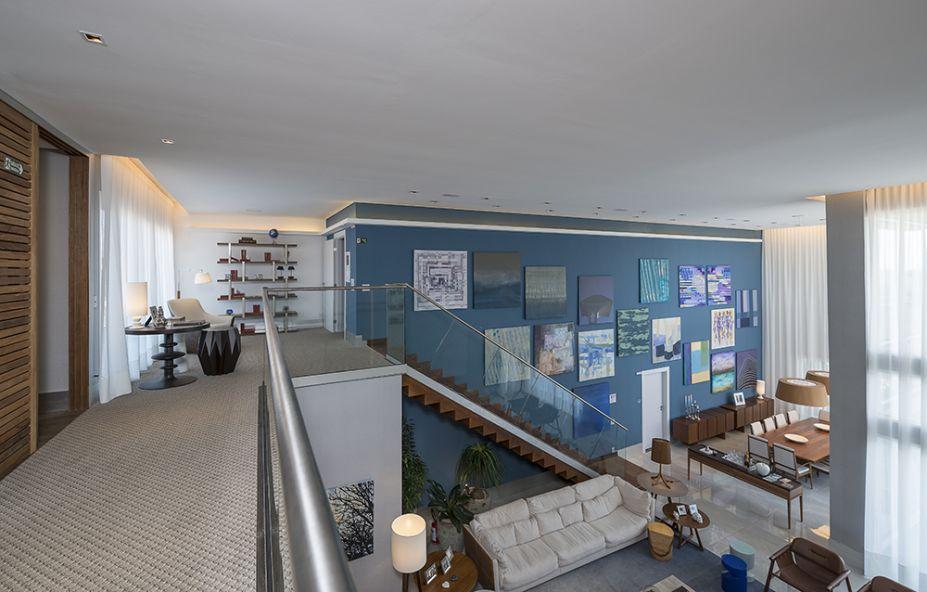<span>Escada e Sala de Leitura - Daniele Guardini e Adriano Stancati. A escada foi revestida em madeira e possui guarda-corpo de vidro. Os espaços são ligados aos demais cômodos por uma passarela, também em madeira, que desce pela parede e percorre o piso como se fosse sua continuação.</span>