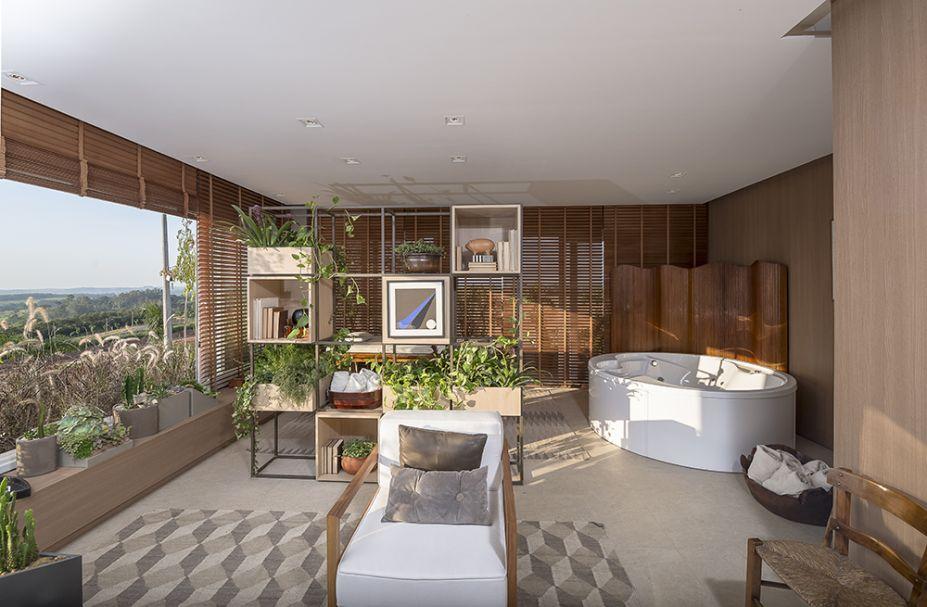 <span>Sala do Bem-Estar - Gustavo Paschoalim e Paulo Azevedo. O espaço pretende ser um refúgio no campo, com tons e materiais nas variações de cru, marrom e cinza. A sala é envolta por vidro, integrando a paisagem, enquanto painéis e paredes foram revestidos em madeira.</span>