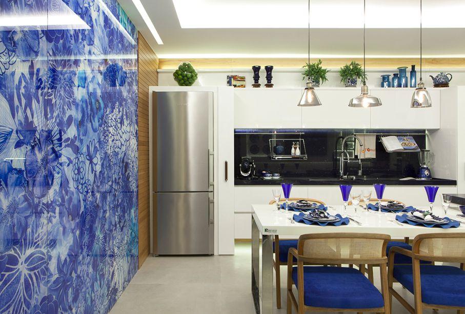 Cozinha do Apartamento Master - Zilda Helal. A parede em vidro, com estampa exclusiva da designer Taiza Ammar, impressa direto no material, é o centro das atenções. Os demais elementos seguem a mesma combinação de cores, mas com linhas discretas, como as bancadas em silestone e a mesa de refeições em nanoglass. O porcelanato com textura cimentícia aparece no piso para equilibrar.