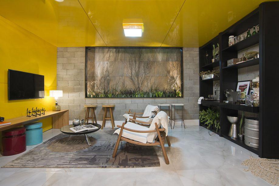 <span>Garagem Renault - Geórgia Vieira e João Dias. Com paredes de blocos de concreto e móveis em madeira, fica clara a influência do estilo industrial. Mas o que seria sóbrio torna-se descontraído com a parede e o teto laqueados em amarelo. Para trazer aconchego, os estofados são em algodão cru e as plantas, vedetes desta CASACOR, são típicos exemplares regionais.</span>