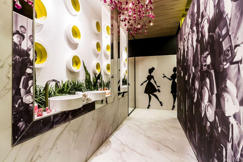 Casa Cor Bolívia 2015: Banheiro feminino por Eliana Céspedes e Natalia Cronembold - Vários espelhos compõem o banheiro feminino público. Portas separam os espaços dos vasos sanitários. Em uma das paredes, janelas circulares remetem à fachada original do colégio Santa Ana. Há ainda um jardim interno.