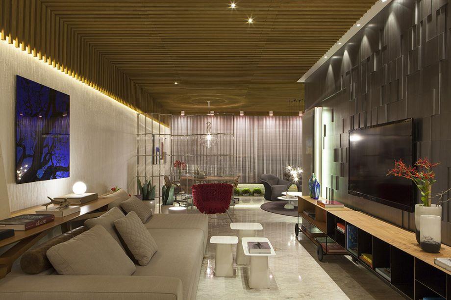 <span>Living do Apartamento - Junior Torezani e Victor Sarcinelli. O ambiente integra salas de TV, de estar e jantar, além de incluir um lavabo. O destaque está nos tons de cinza, que lavam até os tecidos dos móveis, e no jogo com texturas como quartzito, madeiras e papel de parede que envolvem o espaço. Aqui, as cores são adicionadas de forma pontual, como na poltrona Vermelha dos Irmãos Campana. Na sala de jantar, separada por um biombo metalizado, a mesa Bailarina é assinada por Leo Romano.</span>