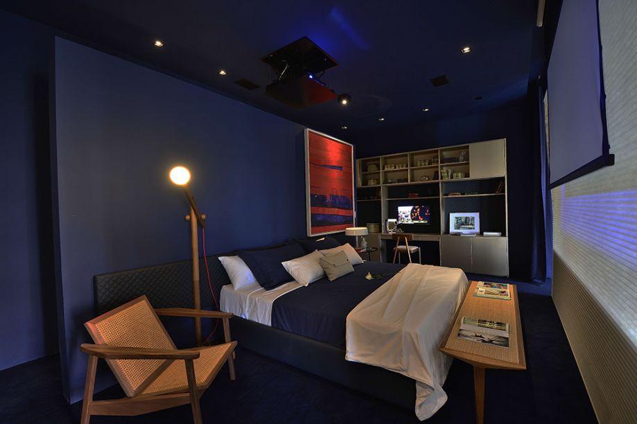 Loft For Life - Dany Bitencourt e Wagner Costa. A área íntima fica em um patamar elevado e traz móveis sob medida da Florense, incluindo os roupeiros com revestimento interno em couro matelassê. O azul profundo lava as paredes e o teto, conferindo profundidade e intimismo ao espaço.
