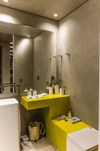 """<span>Lavabo - Flávia Fernandes e Camila Carrasco. Na """"caixa de concreto"""", destacam-se a bancada em quartzo amarelo, a linha de objetos de porcelana desenhada especialmente para o evento e a iluminação aconchegante.</span>"""