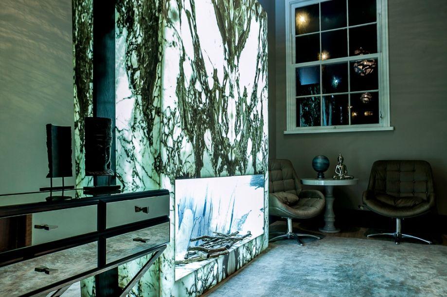 Lounge GOSEG – Manu Cancela. Trata-se de um ambiente contemporâneo e funcional, em tons de bege, dourado, azul e madeira. A cor azul petróleo das almofadas e objetos decorativos traz tranquilidade. O dourado traz um toque clássico e mais sofisticado nas molduras ao redor da televisão. Tons perolados foram usados no tapete e papel de parede, com toques dourados. O mobiliário embutido foi todo projetado e planejado para otimizar os espaços. Painéis de madeira se destacam no projeto.