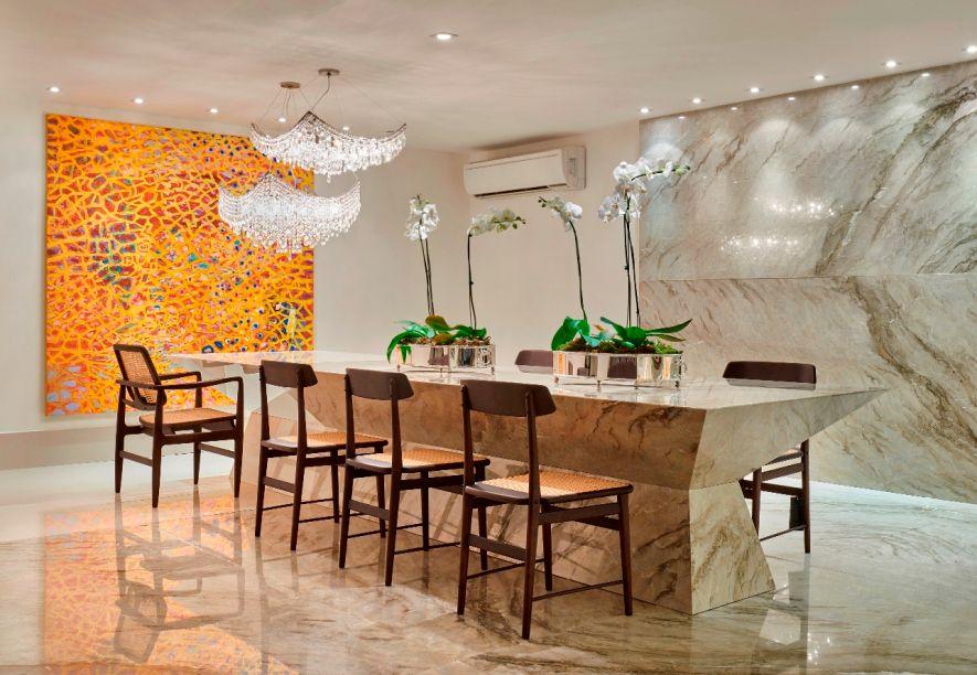 Sala de Jantar - Nando Nunes. O mármore crema é o elemento chave, presente no piso, na parede, na mesa e em um aparador. Seus veios bastam e dispensam o excesso de objetos, gerando um espaço limpo e elegante.