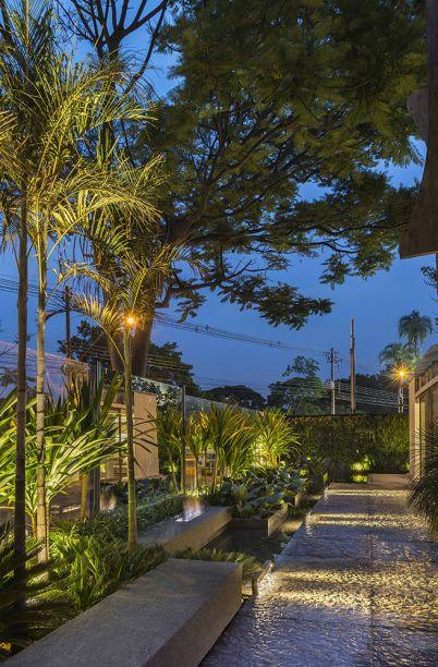 Jardim Café - Mara Rubia. Com 141m², o espaço celebra a água, a terra, o fogo e o ar. A iluminação destaca os principais elementos, sendo um deles a lareira ecológica revestida em mármore polido e fragmentos de rochas ornamentais.