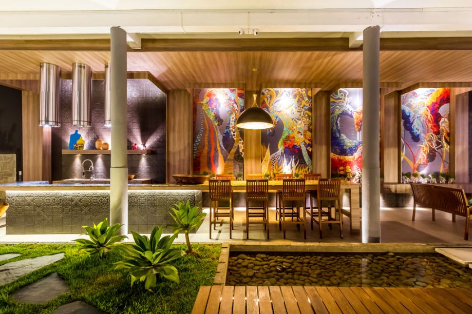 Casa Cor Bolívia 2015: Ponto de encontro por Laura Ponce de León - O espaço gourmet traz uma cozinha aberta, aproveitada em sua altura e comprimento, para criar um restaurante ao ar livre. É um ambiente acolhedor que convida à permanência do visitante. A arquiteta apostou no uso de texturas e no colorido das impressões digitais do artista Koqui Handall. O espaço foi inspirado na marca Tramontina pelo uso de mobiliário e utensílios para cozinha de última geração.