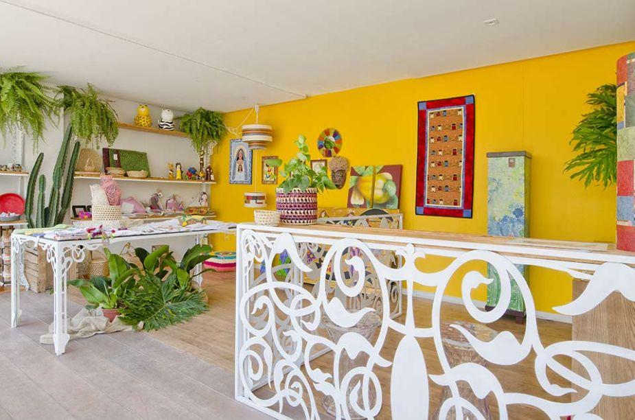 Espaço Sebrae - Denis Cadena, Angélica Garcia e José Neto. As peças expostas ganham destaque diante da base em amarelo e branco. Os móveis são trabalhados e recortados com formas orgânicas e naturais, em sintonia com um ambiente que valoriza a beleza do feito à mão.