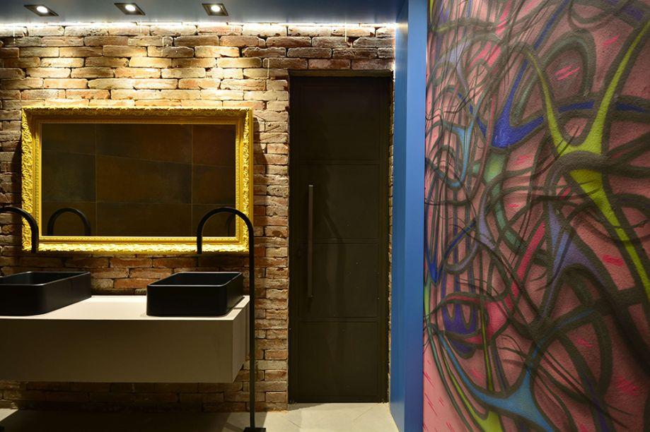 Lavabos do Café – Natalia Schäffer. O ambiente de 13,35m² trazia como desafio suas formas recortadas antes pouco aproveitadas. O layout trouxe funcionalidade ao espaço, que incorporou o estilo urbano nos tijolos aparentes, no concreto e principalmente na parede grafitada.