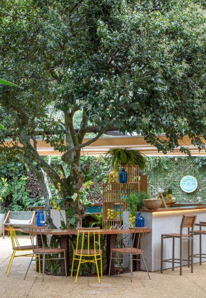 <span>Bar de Gin - Fernanda Sampaio, Júlia Sampaio e Raísa Rodrigues. Tudo acontece em torno da árvore existente. De forma orgânica, o balcão se molda ao redor e seu desenho aproxima quem estiver no bar do paisagismo, além de integrar diversos ambientes de estar. Módulos em madeira compõem estantes leves e funcionais, que abrigam desde plantas até frutas e utensílios.</span>