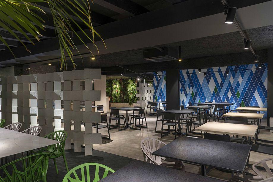 Restaurante - Studio HuB. Os elementos modernistas da cidade são reverenciados no ambiente de 190m², a começar pela linha de móveis e as artes dos murais, ambas assinadas pelo Studio HuB. Lounge, varanda, bar e salão de refeições se conectam visualmente pelo uso de materiais em comum, como concreto, piso vinílico e painéis em MDF.