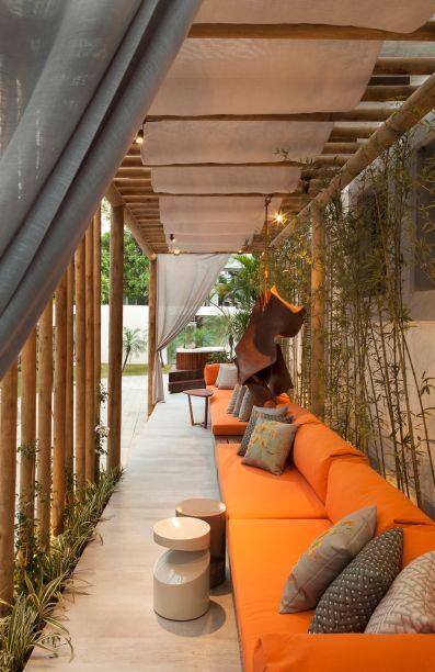 <span>Varanda Boulevard - Juliana Dijck e Marcela Muniz. Na transição entre a casa e o jardim foi criado um espaço contemplativo, reservado pelo pergolado em madeira. Ele garante a visão da paisagem e ao mesmo tempo protege do sol, com o auxílio de tecidos crus que atuam na cobertura. Estofados generosos na cor laranja conferem modernidade.</span>