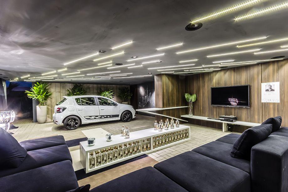 CASA COR CAMPINAS 2016. Garagem Renault - Christie Cornelio. O arquiteto adotou concreto, lajes rústicas e um piso de alto tráfego combinado com tapetes. A iluminação enfatiza o desenho vanguardista, que lembra velocidade.