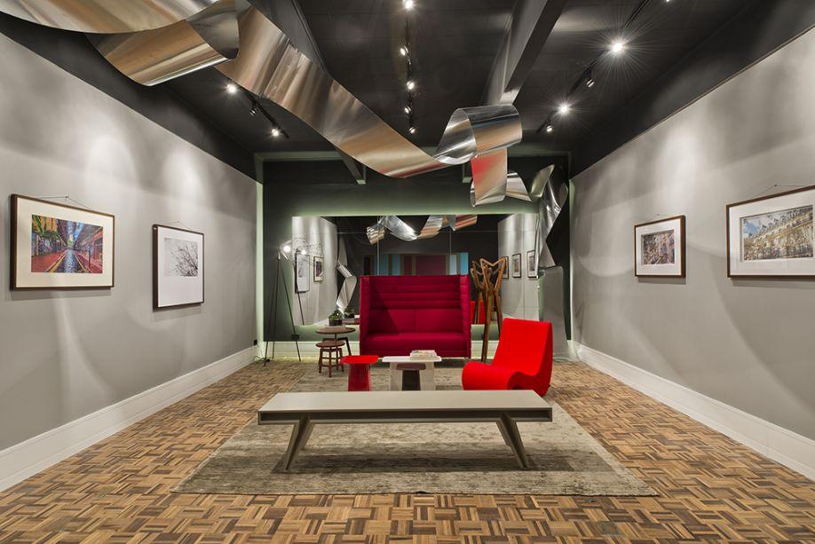 Instalação de Arte Fotográfica - André Bertoluci. Pensado para exposições fotográficas, o espaço de 35 m² foi idealizado como uma galeria, com teto e duas paredes na cor preta. Lâmpadas dicróicas são direcionadas aos elementos de destaque. Ao fundo, o painel de espelho com iluminação de fundo parece flutuar e reforça o destaque à arte. Todo o mobiliário conceitual é italiano, da marca Vitra - com destaque para o sofá Alcove Highback -, fornecido pela Inove Galeria. Outro elemento de design é a escultura metálica da artista plástica Marilene Ropelato, que remete aos negativos de filmes fotográficos.
