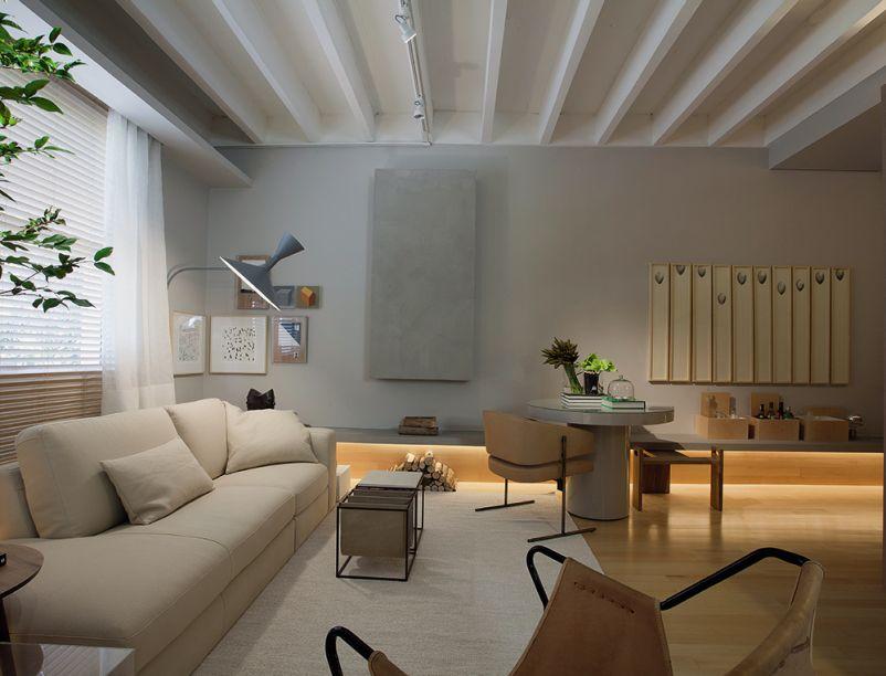 Estúdio Jabuticaba - Nildo José. O banco multifuncional de concreto contorna o espaço e é peça-chave do loft de 43m2. Ele faz as vezes de chapelaria, aparador, prateleira, apoio da lenha da lareira e banco da mesa de jantar.