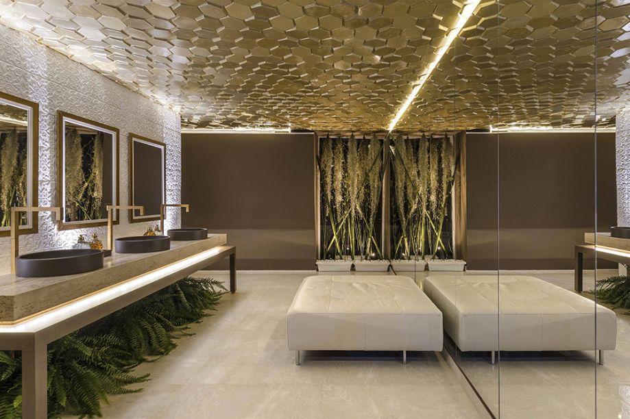Lavabo Gold – Wesley Monteiro e Luisa Costa (LW Engenharia e Design). Inspirado no Restaurante Gold, em Milão, o espaço investe nas formas geométricas em 3D. No teto, entram em cena placas de gesso em formato hexagonal pintadas em dourado. Uma das paredes foi revestida com porcelanato HD que lembra uma renda - ela é refletida no espelho do lado oposto, que duplica visualmente o ambiente de 20m².