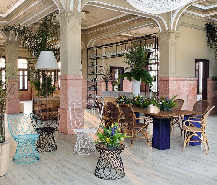 Restô Bar CASA COR - Ro de Rivero. O estilo orgânico marca presença na vegetação de grande porte, que acompanha a altura do pé direito, e no uso de materiais naturais como a madeira, trazendo a sensação de um espaço ao ar livre.