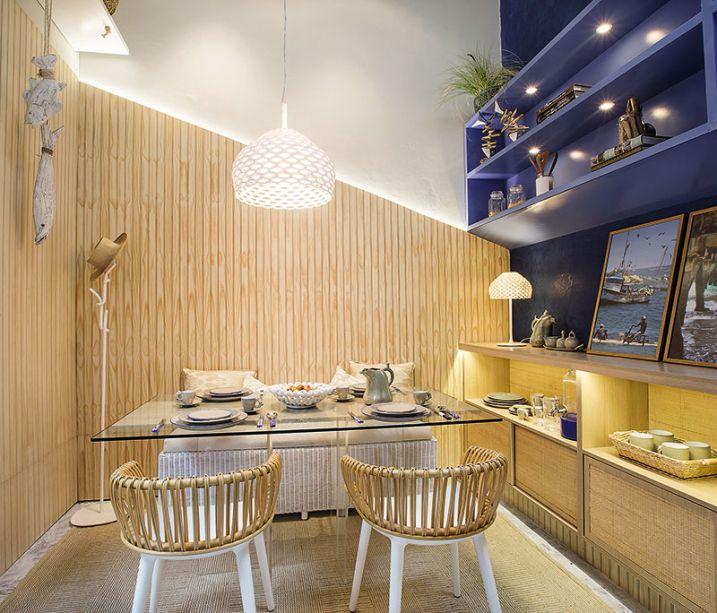 Sala de jantar - Andrea Ulloa e Brenda Middlebrook. A paisagem do norte peruano inspirou a proposta das arquitetas, que recriam as paisagens como um caminho pelo bosque seco com destino ao mar. É o que se imagina ao encontrar as cores cálidas e a madeira nas paredes em sintonia com o azul profundo que confere amplitude ao espaço.