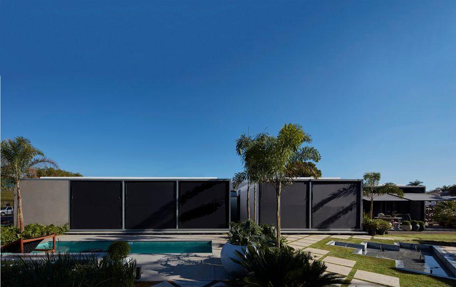 <span>Casa Pré-Fab, por Bruno Campos, Marcelo Fontes e Silvio Todeschi (BCMF Arquitetos). O desafio de criar uma boa impressão a respeito de casas pré-fabricadas foi respondido nesta construção de alto padrão. Com 230m2 e um único pavimento, foi estruturada em oito módulos, completados por outros componentes de acordo com a orientação do terreno. Uma sequência linear organiza os espaços, intercalados com mini-pátios, conectando três suítes, sala de TV, living, sala de jantar, cozinha, área de serviço, lavabo, escritório, piscina e garagem para quatro carros.</span>