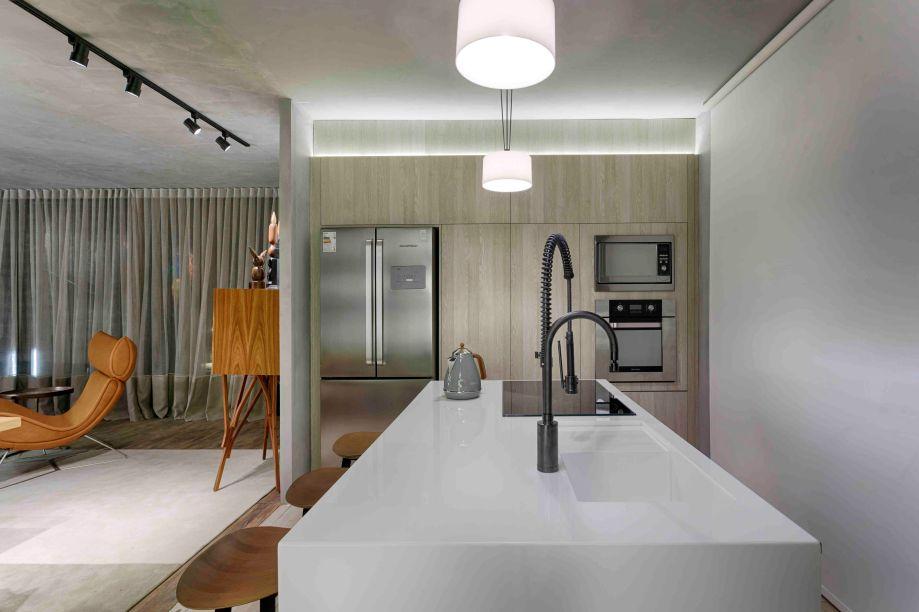 Cozinha - Camila Ferreira. O ambiente faz parte de um conjunto que também engloba sala de banho e área de serviço. Aqui o espaço é fresco e clarinho, com piso em porcelanato madeirado, no mesmo padrão da marcenaria, para aquecer. O contraste vem nas bancadas brancas em Nanoprime, um composto de vidro.