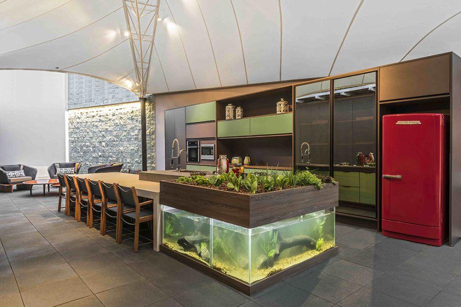 """<span>Cozinha Contemporânea - Valéria Alves. A inovação está no tanque de peixes, sob a horta em L que abraça a bancada em Dekton. É aquela história de """"caçar para comer"""" que se quer contar. Mas há um apelo sustentável: a água e o alimento dos peixes e insumos da horta são reaproveitados e um alimenta o outro. A cobertura em lona tensionada protege o ambiente e mantém o contato com o exterior, com móveis em palha sintética.</span>"""