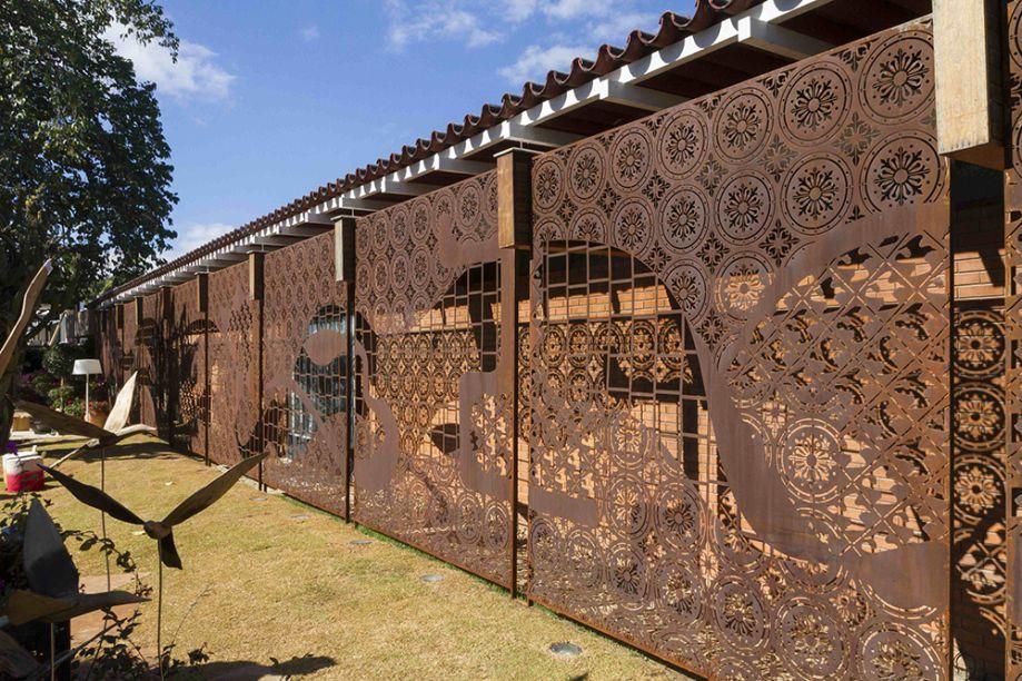 Fachada e Jardim de Saída - Paulo Pontes. O painel em aço corten, de 30m x 3m, tem concepção do artista Léo Arruda. A intervenção delicada não esconde a fachada original da casa, de 1969.