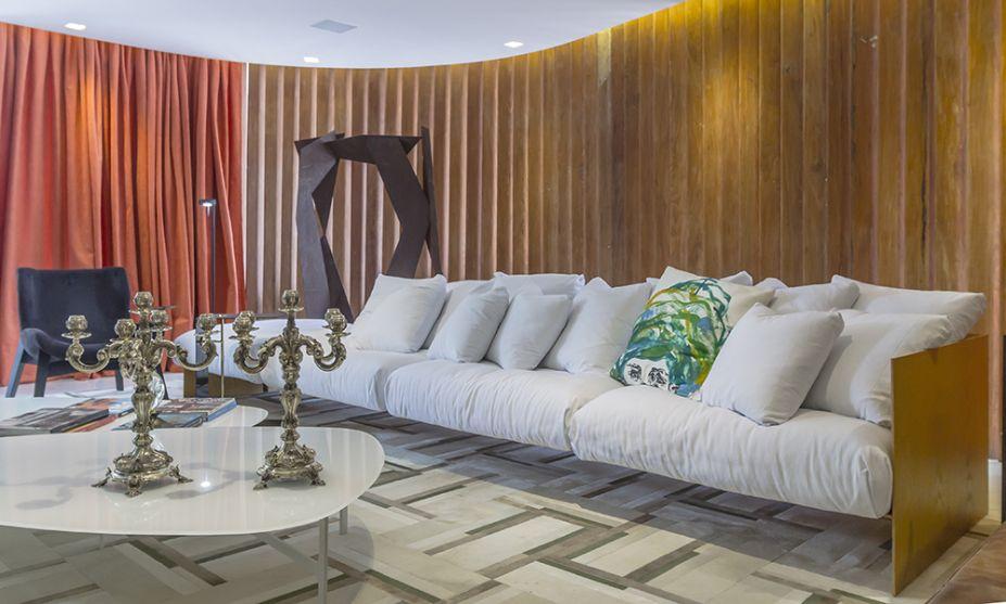 Living Borsoi – Renato Teles. Os brises em madeira são outro item original preservado, valorizado pelo generoso sofá que ocupa toda a extensão do ambiente.
