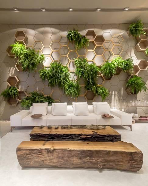 <span>Living Garden – Sandra Moura e Leila Azzouz. Com pé direito elevado, as paredes ganham destaque. Uma delas recebe a instalação de hexágonos produzidos em laca fosca, madeira e estrutura de ferro pintada. Ela abriga um delicado jardim vertical.</span>