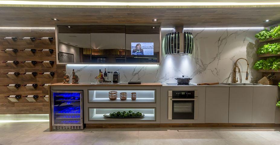 Living Gourmet – Anabel Alvarez. Integrada à sala, a cozinha recebe o mármore em uma parede inteira e modulados espelhados. Eles, inclusive, oferecem uma visão do que se passa no restante do espaço. Fitas de LED destacam as formas lineares e funcionais do ambiente enquanto promovem uma luz indireta.