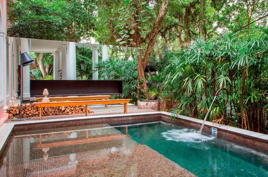 CASACOR Rio de Janeiro 2016. Varanda - Maurício Nóbrega. Ao fundo, um deck reúne três piscinas da iGUi em fibra pastilhada verde, dispostas em níveis diferentes. Por trás, um grande banco com espelho e um nicho para fogo, que aquece o local.