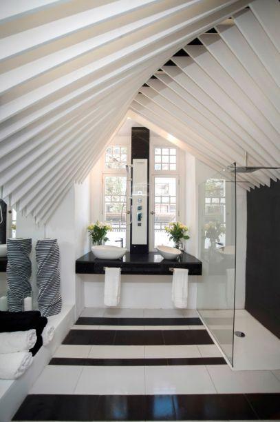 Movimiento Perpetuo - Christian Wiese (Briggs). O teto é um elemento escultural fundamental nesta sala de banho, que acentua o apelo gráfico das linhas retas com o duo preto e branco. Mas um toque de assimetria se fez necessário e vem no par de cubas diferentes.