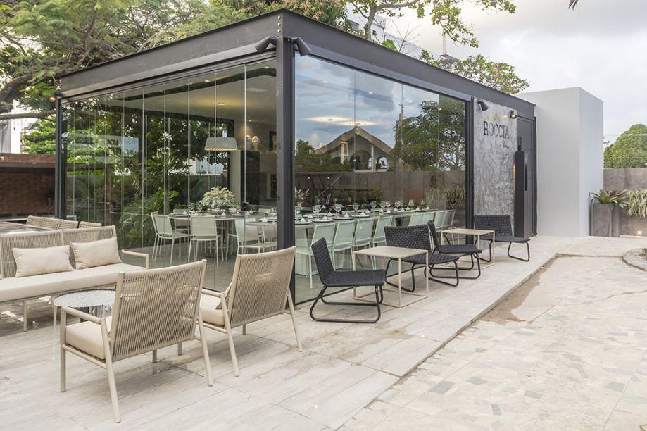 Restaurante – Rayssa Lira. A integração é total com a área externa, graças a generosas aberturas resguardadas pelo vidro. Móveis baixinhos ao estilo lounge compõem uma ambientação informal.