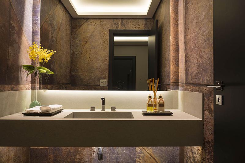 No lavabo, a cuba é de limestone bateig blue. O papel de parede reproduz chapas de zinco oxidadas.