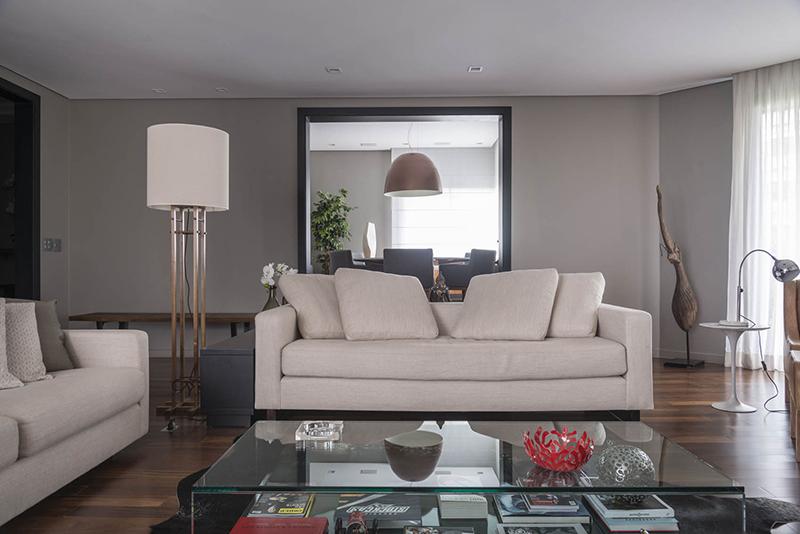 Os revestimentos de madeira, os tons mais escuros nas paredes e iluminação intimista, com lâmpadas dimerizáveis tornam o ambiente confortável e intimista, próprio para relaxar ou receber.
