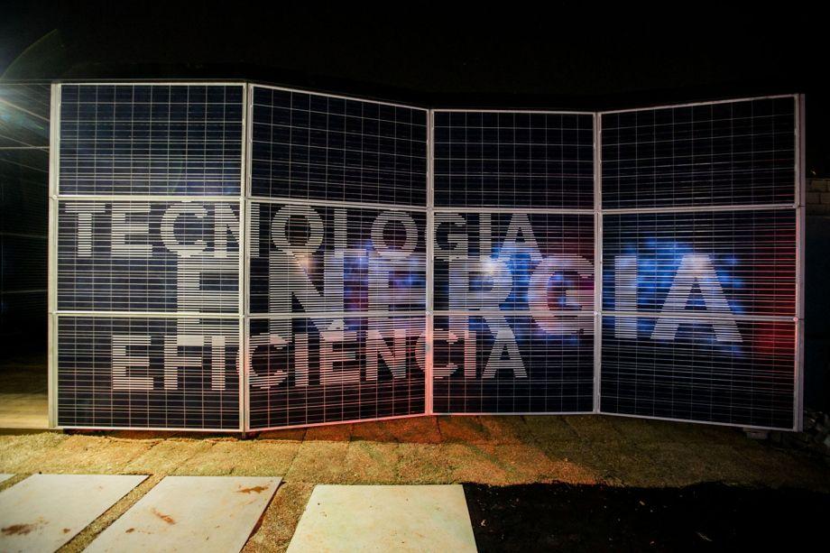CASACOR Minas Gerais 2016. OptPower, por Silvio Todeschi, Ana Bahia e Mariana Hardy. Situado dentro de um container, o espaço é responsável por toda a energia usada na CASA COR Minas - gerada através da captação dos raios solares e fornecida pela empresa OptPower. Os profissionais exploraram o uso dos próprios painéis de energia fotovoltaica para envelopar e revestir toda a estrutura do ambiente. No seu interior, está localizado o maquinário que distribui a eletricidade para a sede e a fachada recebeu um trabalho tipográfico e um videowall informando sobre a tecnologia e o produto utilizado.