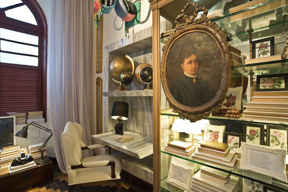 CASACOR Ceará 2016. Biblioteca - Roberto Pamplona. A escrivaninha foi desenhada em um nicho de mármore. As muitas estantes são repletas de livros, muitos encapados com linho branco e tecidos brocados dourados.