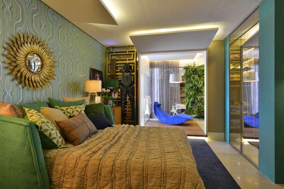 Suíte da Filha - Márcia Andréa. O papel de parede exclusivo na cor verde confere frescor ao visual e conecta os espaços da suíte. O banheiro se integra naturalmente e, com o auxílio do painel em madeira, transforma-se em um SPA. O jardim suspenso afirma o clima de brasilidade.
