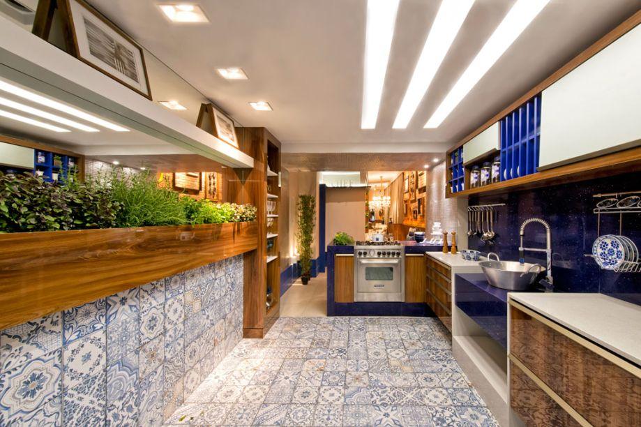 Loft da Gourmet. A arquiteta e urbanista Tatielly Zammar destaca a cozinha do projeto, que se integra à sala de jantar e aos demais ambientes por meio da ilha gourmet. As bancadas possuem superfície em quartzo, e a marcenaria leva painéis em madeira certificada. O piso e a parede ganham o charme do porcelanato Blue Memory. Os utensílios da cozinha estão sempre à mão, em barras de inox. E a horta oferece sempre temperos frescos.