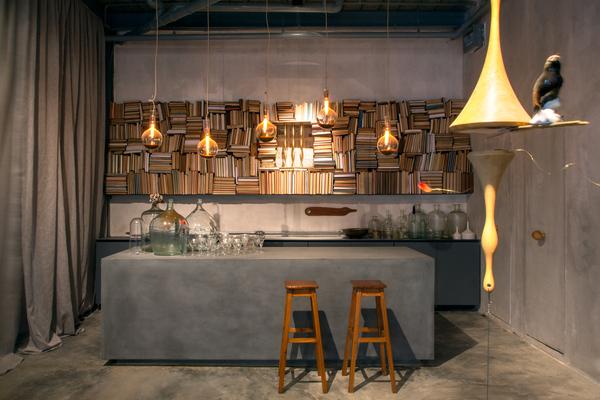 Ao Ganso Azul Bar - Bruno Carvalho e Camila Avelar. Piso e teto de cimento foram mantidos para abrir espaço ao lounge, transformado em laboratório de experiências sensoriais. Livros encaixados compõem um enorme painel atrás do bar.