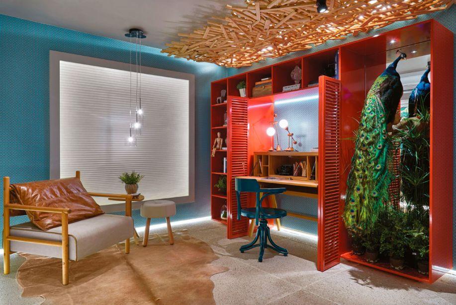 Home Office - Andréia Spessatto Baratto e Náira Sá - O home office ficou com jeito de sala de estar e leitura, graças ao estilo praiano e ao uso de cores que quebram a sobriedade, como o azul que lava o papel de parede e o vermelho na marcenaria. O móvel, aliás, abriga um pavão taxidermizado. Parte do teto ganhou cobertura em madeira reflorestada, inspirada em uma das poltronas mais conhecidas dos Irmãos Campana.