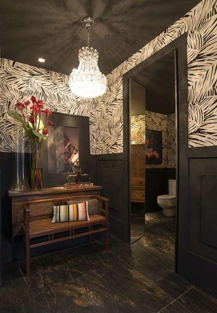 Banheiros Públicos - Érico Monteiro. As paredes foram trabalhadas com boiseries e, na metade superior, revestidas com tecidos tropicais em preto e branco. No mobiliário, elementos clássicos definem uma linguagem sofisticada.