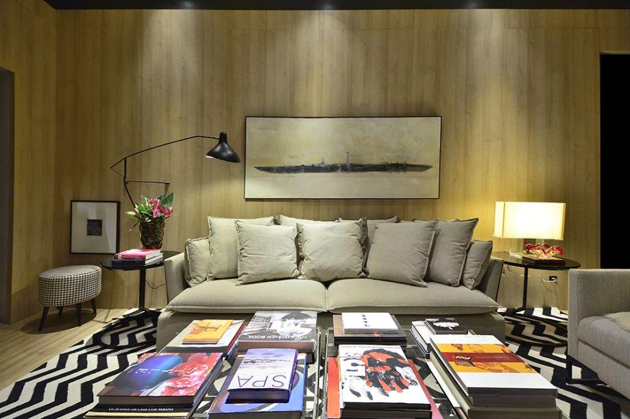 CASACOR Rio Grande do Sul 2016. Para ler e beber - Luiz Sentinger. No outro recanto, prevalece o calor da madeira nas paredes nos painéis Duratex. O estofado modular em linho e o tapete geométrico compõem o espaço, junto com a luminária de mesa Miss K, de Philippe Starck para a Floss.